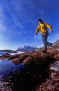 Young man in yellow jacket hiking in rocky terrain with mountain view Stock Photos