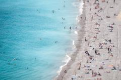 ocean beach with people bathing and tanning. - stock photo