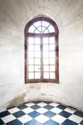 grungy arched window inside old building. - stock photo