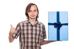 Stock Photo of man with big present showing thumb up