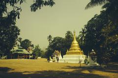 golden thai buddhist temple in the village of pai mae hong son - stock photo