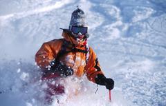 Aktiivinen mies oranssi takki hiihto puuterilunta vuorilla talvella Kuvituskuvat