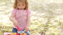 Happy little girl with play kitchen in the park/garden - stock footage