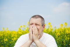 Man keep hands near nose on canola field - stock photo