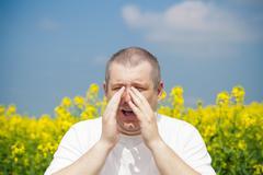 Man sneezes on canola field - stock photo