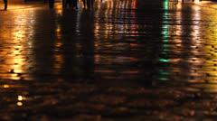 Wet asphalt, people feet and light reflection Stock Footage