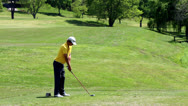 Stock Video Footage of young golfer teeing off tee box back view