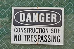 danger, construction site, no trespassing as warning message on metal grid - stock photo