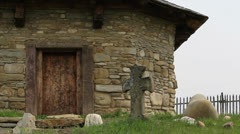 Stone grave cross and stone church Stock Footage