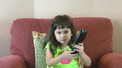Frustrated little girl with tv remote trying to change the channels Stock Footage