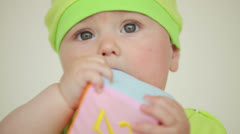 Baby in bright clothes chew toy Stock Footage