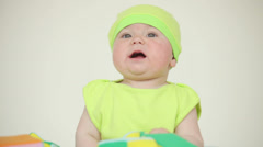 Baby with a cap playing with a ball Stock Footage