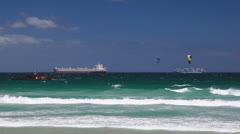 Cargo Ships on Ocean Close to Breaking Waves with Kite Surfers Stock Footage