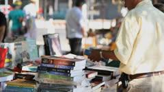 Customer looks at books on sale at Porto Alegre's Flea Market (FleaMkt 38) Stock Footage