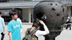 Japanese children near incense burner in Kamakura city, Japan Stock Footage