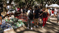 Shoppers look at vintage items at Porto Alegre's Flea Market kiosks(FleaMkt 25) Stock Footage
