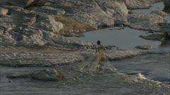 African boy in water with net, catching fish. Niassa Reserve, Mozambique. Stock Footage