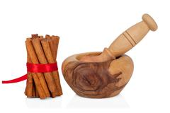 Cinnamon with mortar and pestle on white Stock Photos