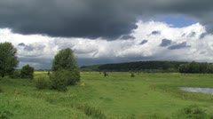Dark clouds above Dutch river landscape, Grebbeberg in background Stock Footage