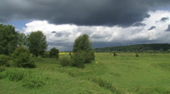 Hold + pan - Dark clouds above Dutch river landscape + moraine hill Stock Footage