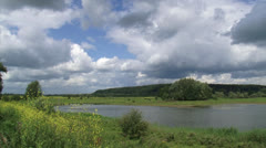 Cumulus clouds above Dutch river landscape, moraine hill at horizon Stock Footage