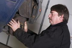 automotive technician manually pulls rotor checking brakes auto repair shop - stock photo