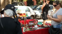 Shoppers look carefully at vintage items on sale at the Flea Market (FleaMkt 24) Stock Footage