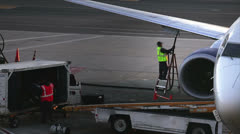 Man is loading luggage onto airplane Stock Footage