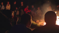 young people gathered around campfire  - stock footage
