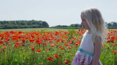 Cute and pretty little blonde girl spending time in a meadow full of poppies Stock Footage