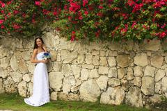 young woman in wedding dress posing in front of the stone wall with flowers - stock photo