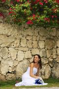 Young woman in wedding dress posing in front of the stone wall with flowers Stock Photos