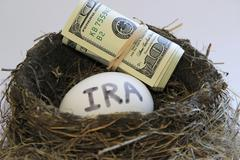 nest with money and egg with ira on it - stock photo