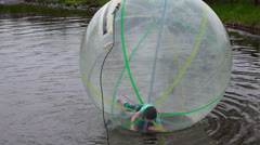 Girl trying a zorb ball Stock Footage
