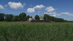 Polder pan to Schokland Village and Church behind Wooden seawall Stock Footage