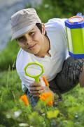 Enfant observant la nature avec une loupe Stock Photos
