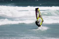 Rear view of young windsurfer in action - stock photo