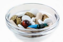 Many various pills in glass bowl Stock Photos