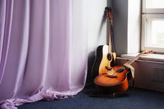 two acoustic guitar next the window - stock photo