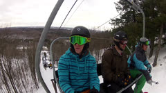 Snowboarders mid chairlift run Stock Footage