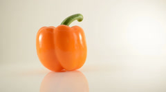 Rotating Orange Pepper On Acrylic Against White - Dolly Left Stock Footage