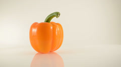 Rotating Orange Pepper On Acrylic Against White - Dolly Right Stock Footage