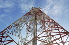 red and white tower of communications with their telecommunications antennas - stock photo