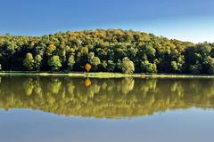 idyllic autumn reflections on lake surface - stock photo
