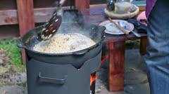 Uzbek pilaf  preparation on open fire stove Stock Footage