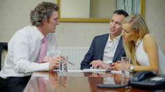 Attractive young couple in discussion with their financial advisor - stock footage