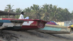 India Tamil Nadu Mahabalipuram man watches in beached boat 5 Stock Footage