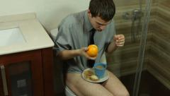 Funny man eating orange on the toilet Stock Footage
