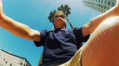Low Angle- Man Rides Bike Under Tall Palm Trees, Office Buildings Stock Footage