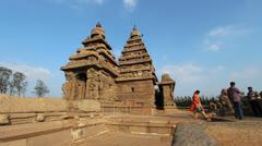India Tamil Nadu Mahabalipuram Shore Temple boy plays near two gopurams 5 Stock Footage